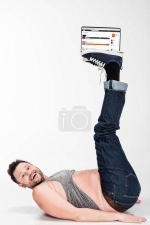Photo pour Excité homme en surpoids regardant la caméra et tenant avec les jambes ordinateur portable avec site Web soundcloud à l'écran - image libre de droit