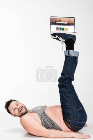 Photo for Excited overweight man looking at camera and holding with legs laptop with shutterstock website on screen - Royalty Free Image