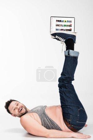 Photo pour Excité homme en surpoids regardant la caméra et tenant avec les jambes ordinateur portable avec youtube site à l'écran - image libre de droit