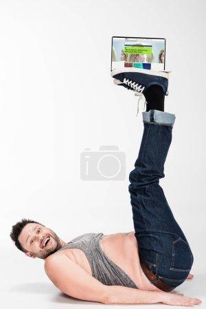 Photo pour Excité homme en surpoids regardant la caméra et tenant avec les jambes ordinateur portable avec bbc site à l'écran - image libre de droit