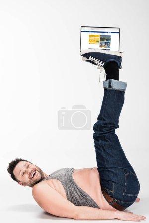 Photo pour Excité homme en surpoids regardant la caméra et tenant avec les jambes ordinateur portable avec site de réservation à l'écran - image libre de droit