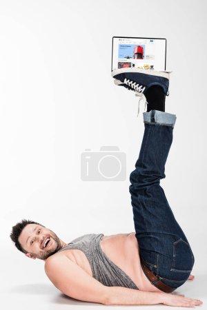 Photo pour Excité homme en surpoids regardant la caméra et tenant avec les jambes ordinateur portable avec site Web ebay à l'écran - image libre de droit