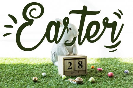 Photo for Decorative rabbit, wooden calendar with 28 April date, and colorful Easter eggs on green grass with Easter lettering - Royalty Free Image