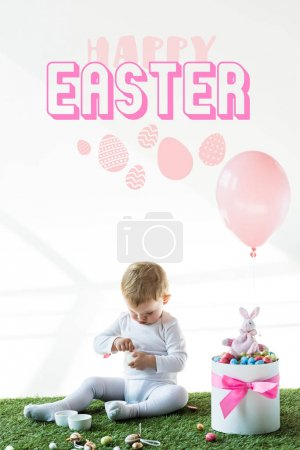 Photo for Cute baby sitting near box with colorful quail eggs, toy rabbit and air balloon on white background with happy Easter lettering - Royalty Free Image