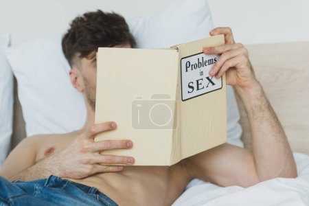 Photo for Selective focus of shirtless man in blue jeans reading problems in sex book while lying in bed - Royalty Free Image