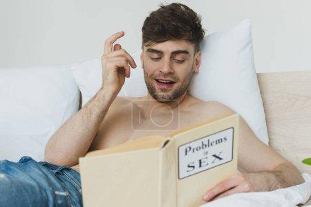 Photo pour Foyer sélectif de l'homme torse nu beau affichant le signe d'idée tout en lisant des problèmes dans le livre de sexe - image libre de droit