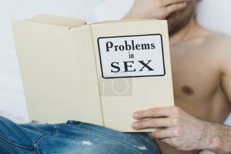 Photo for Cropped view of shirtless man lying in bed and reading problems in sex book - Royalty Free Image