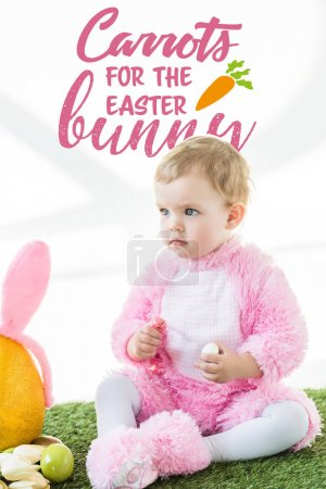 Photo for Cute baby in bunny costume sitting on green grass with carrots for the Easter bunny lettering above - Royalty Free Image