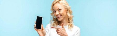 Photo pour Femme blonde gaie de projectile panoramique pointant avec le doigt au smartphone avec l'écran blanc d'isolement sur le bleu - image libre de droit