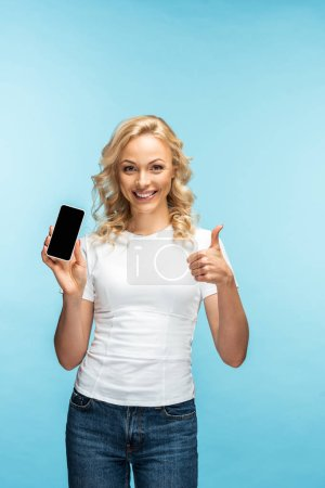 cheerful blonde woman showing thumb up while holding smartphone with blank screen on blue