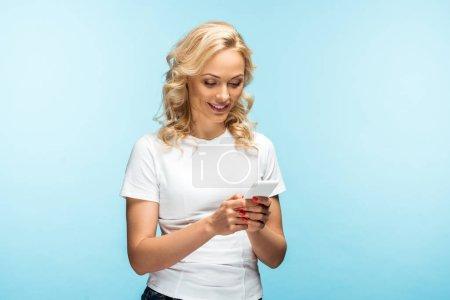 Photo pour Femme blonde gaie en utilisant smartphone et debout sur le bleu - image libre de droit