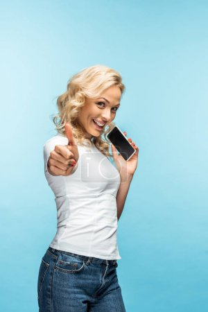 Photo for Attractive blonde woman showing thumb up while holding smartphone with blank screen on blue - Royalty Free Image