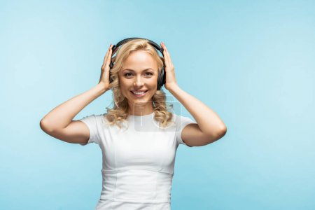 Photo pour Femme blonde heureuse écoutant de la musique et touchant écouteurs noirs sur bleu - image libre de droit