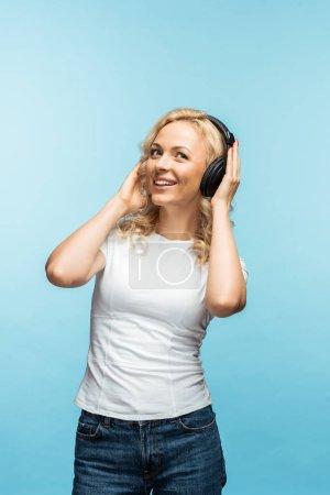 happy blonde woman listening music in black headphones on blue