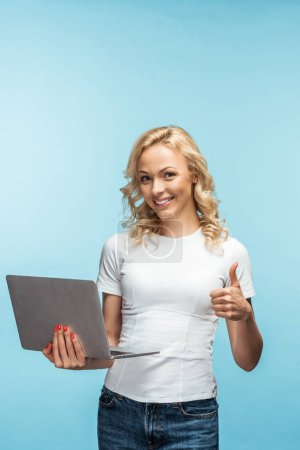 Photo for Happy curly blonde woman holding laptop while showing thumb up on blue - Royalty Free Image