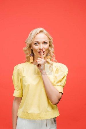 Photo pour Femme blonde gaie regardant l'appareil-photo et affichant le signe de silence sur le rouge - image libre de droit