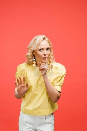 Photo pour Femme blonde attirante regardant l'appareil-photo et affichant le signe de silence sur le rouge - image libre de droit