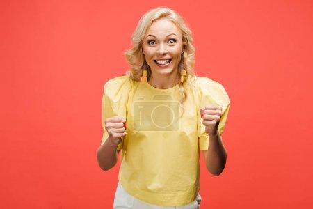 Foto de Happy blonde woman looking at camera and celebrating success on red - Imagen libre de derechos