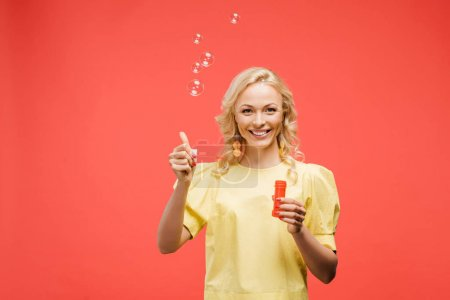 cheerful blonde woman holding bottle near soap bubbles and showing thumb up on red