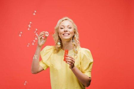 Foto de Mujer rubia alegre sosteniendo botella cerca de burbujas de jabón y sonriendo en rojo - Imagen libre de derechos