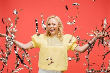 Photo pour Heureuse blonde femme souriant près de argent brillant confettis sur rouge - image libre de droit
