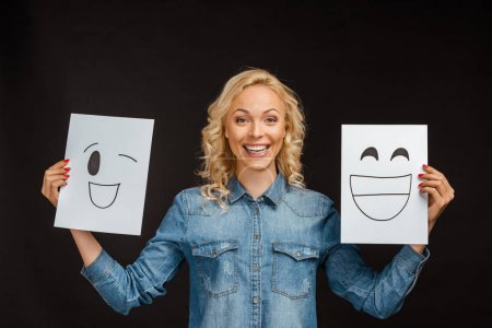 cheerful blonde woman holding papers with happy faces isolated on black
