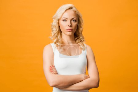 Foto de Serious curly blonde woman looking at camera while standing with crossed arms isolated on orange - Imagen libre de derechos