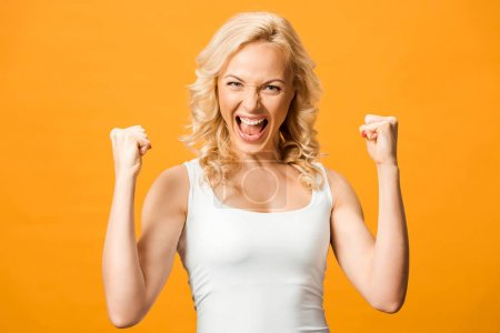 Photo for Excited blonde woman looking at camera and celebrating triumph isolated on orange - Royalty Free Image