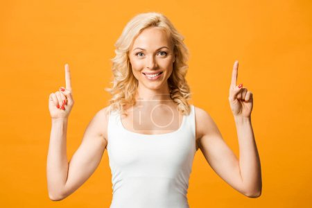 Photo for Beautiful blonde woman looking at camera and pointing with fingers isolated on orange - Royalty Free Image