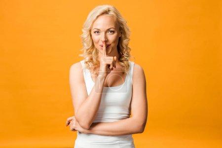 Photo pour Femme blonde gaie regardant l'appareil-photo et affichant le signe de silence d'isolement sur l'orange - image libre de droit