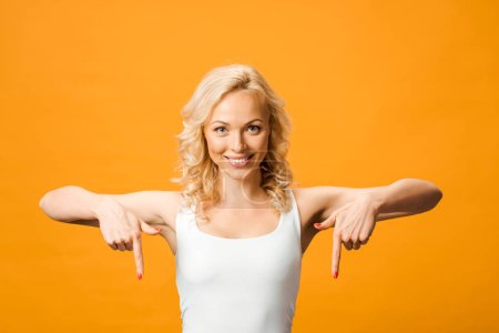 Photo for Attractive woman looking at camera and pointing with fingers isolated on orange - Royalty Free Image