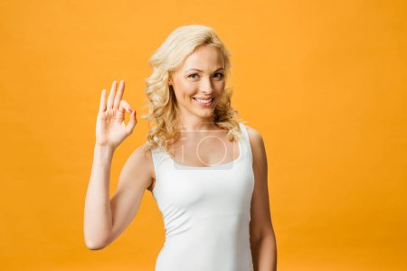 Photo pour Femme bouclée gaie regardant l'appareil-photo et affichant le signe ok d'isolement sur l'orange - image libre de droit