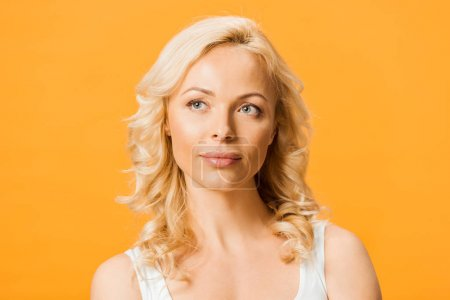 Photo for Beautiful and pensive blonde woman thinking isolated on orange - Royalty Free Image