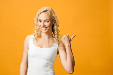 Lächelnde blonde Frau zeigt Daumen nach oben auf orange