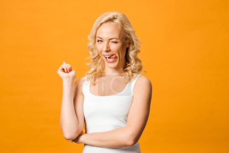 happy blonde woman showing tongue while looking at camera isolated on orange