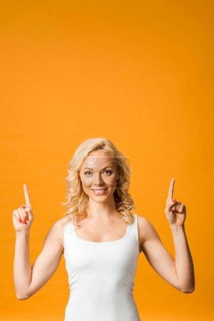 Photo pour Femme blonde souriante pointant des doigts tout en regardant la caméra isolée sur orange - image libre de droit