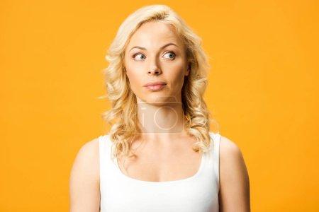 Photo pour Femme blonde surprise en t-shirt blanc isolé sur orange - image libre de droit
