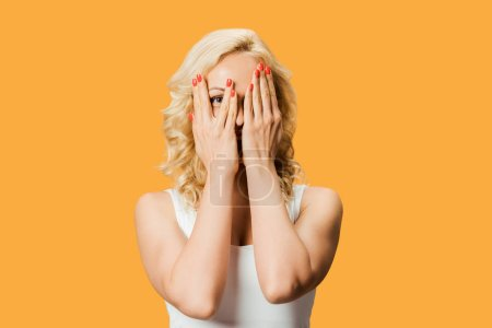 Photo for Curly blonde woman covering face and looking at camera isolated on orange - Royalty Free Image