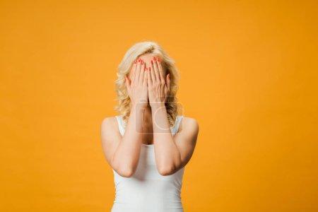 Foto de Curly blonde woman covering face while standing isolated on orange - Imagen libre de derechos