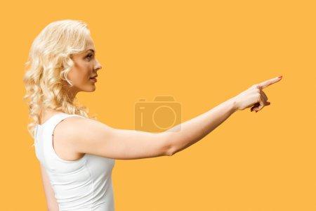 Photo pour Jolie femme bouclée debout et pointant avec le doigt isolé sur l'orange - image libre de droit