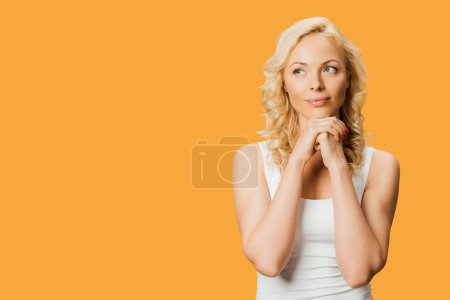 Photo for Pensive blonde woman standing with clenched hands isolated on orange - Royalty Free Image