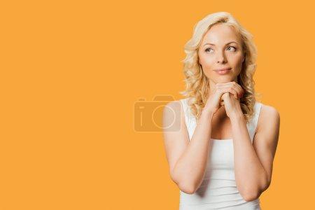 Photo pour Femme blonde pensive restant avec les mains serrées d'isolement sur l'orange - image libre de droit