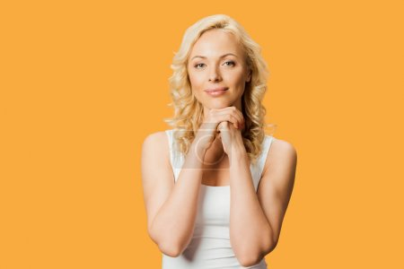 Photo for Beautiful woman looking at camera and standing with clenched hands isolated on orange - Royalty Free Image