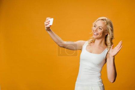 Photo pour Gai blonde femme agitant la main tout en prenant selfie sur orange - image libre de droit