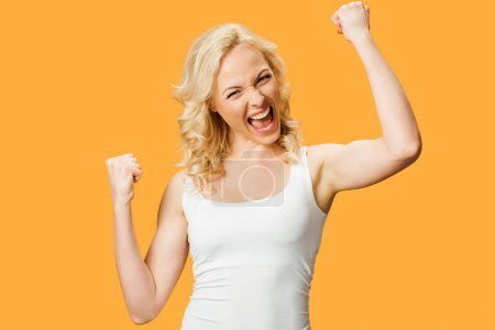 Photo for Happy blonde woman gesturing while celebrating triumph isolated on orange - Royalty Free Image