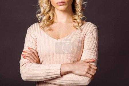 Photo pour Vue recadrée de femme sérieuse debout avec les bras croisés isolés sur noir - image libre de droit