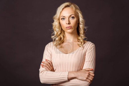 confident attractive woman standing with crossed arms isolated on black