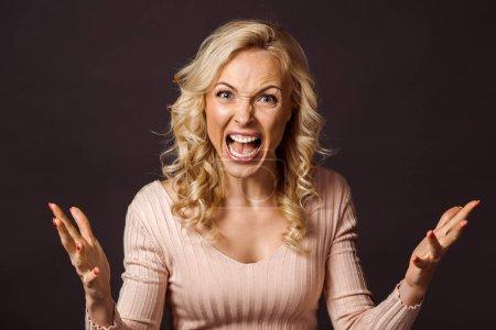 Photo pour Femme blonde émotionnelle gesticulant et criant isolé sur noir - image libre de droit