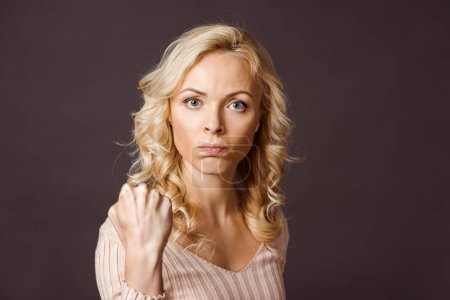 Photo for Angry blonde woman looking at camera and showing fist isolated on black - Royalty Free Image