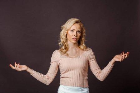 Photo pour Belle femme blonde montrant geste haussant les épaules isolé sur noir - image libre de droit